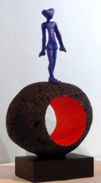 Acróbatas V. 2016. figura de plomo pintada de azul, sobre escultura en piedra volcánica de Manuel Cyphelly. Figura 13 cm